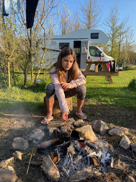 A child toasting marshmallows over an open fire in Wales