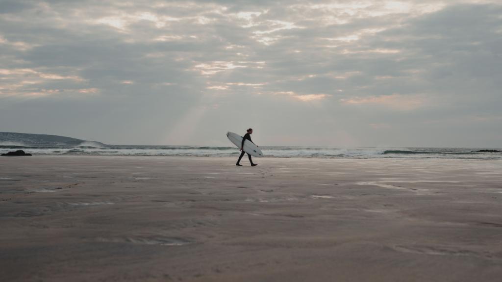 A surfer along the beach at Gunard's Head, Cornwall