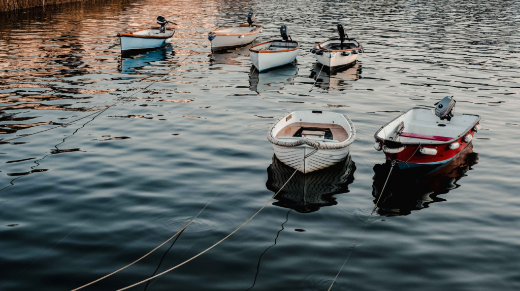 Boats floating on still water at Mullion Cove, Cornwall, England.